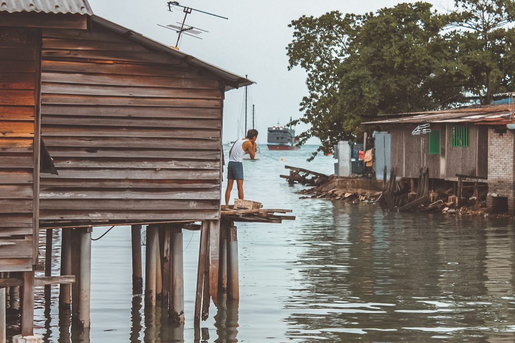 man-outside-his-water-stilit-home-penang-2